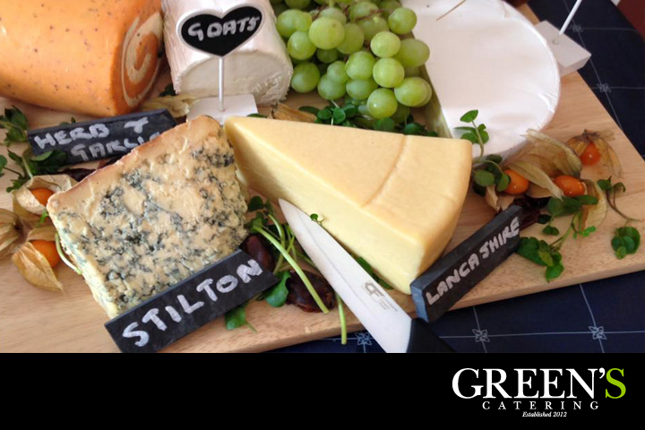 An assortment of cheeses presented on a wooden board.